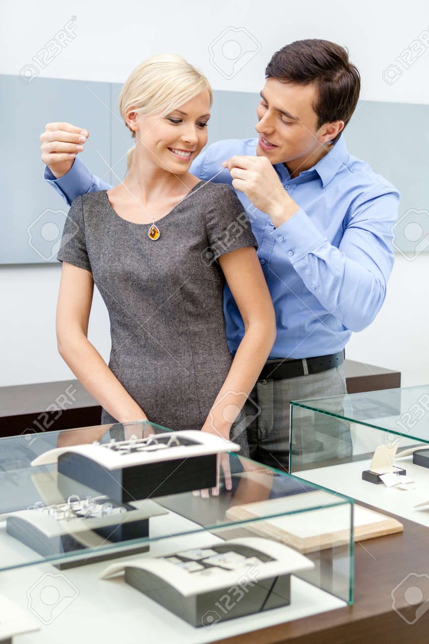 Male puts necklace on his girlfriend at jeweler's shop. Concept of wealth and luxurious life Stock Photo - 22809070
