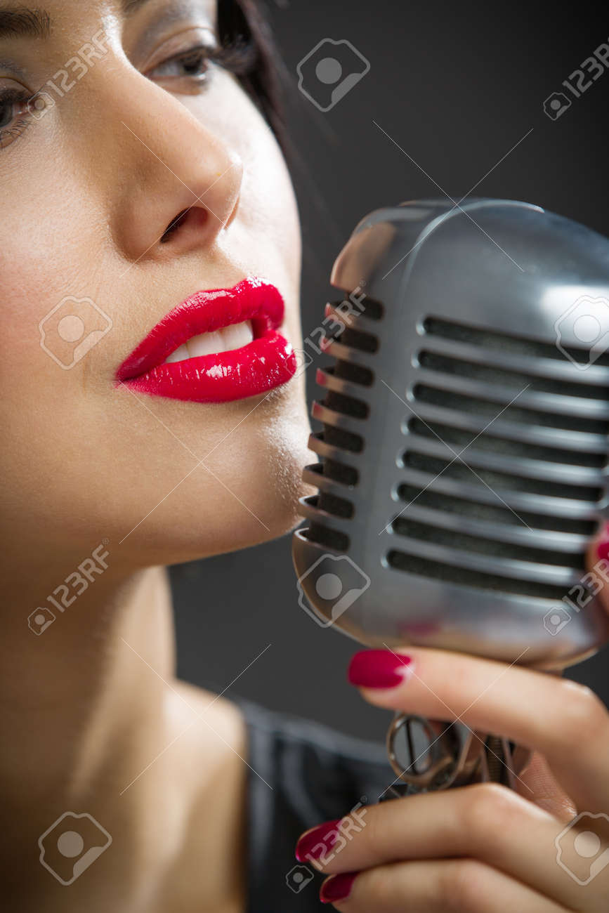 Headshot of female singer keeping microphone on grey background. Concept of music and retro fashion Stock Photo - 23958328