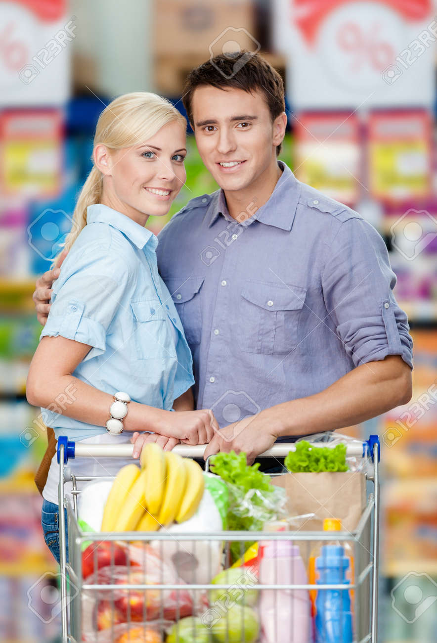 Half Length Portrait Of Couple In The Supermarket With Cart Full