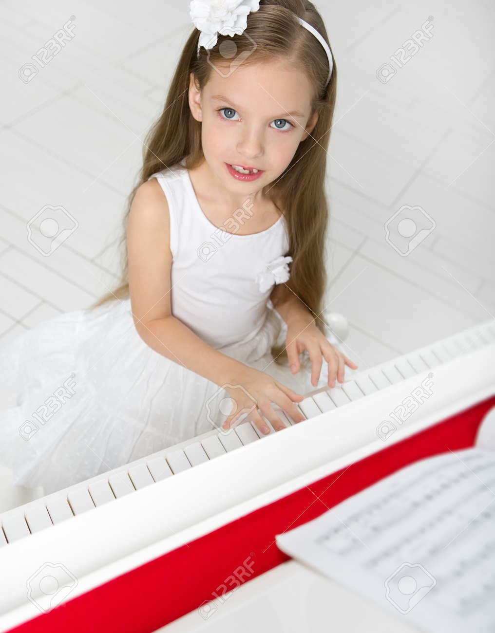 Portrait of girl in white dress playing piano. Concept of music study and leisure Stock Photo - 24481068