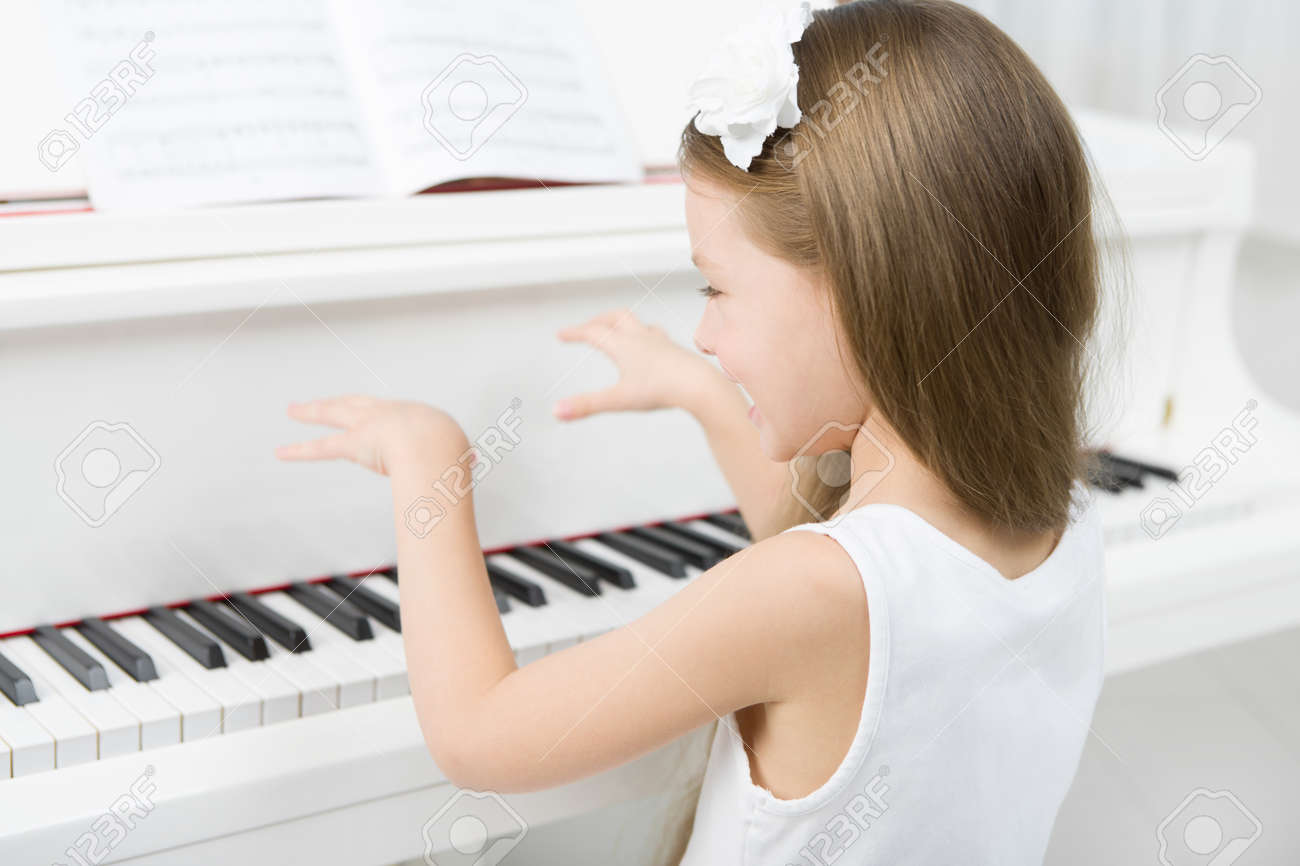 Back view of little girl in white dress playing piano. Concept of music study and art Stock Photo - 24481070