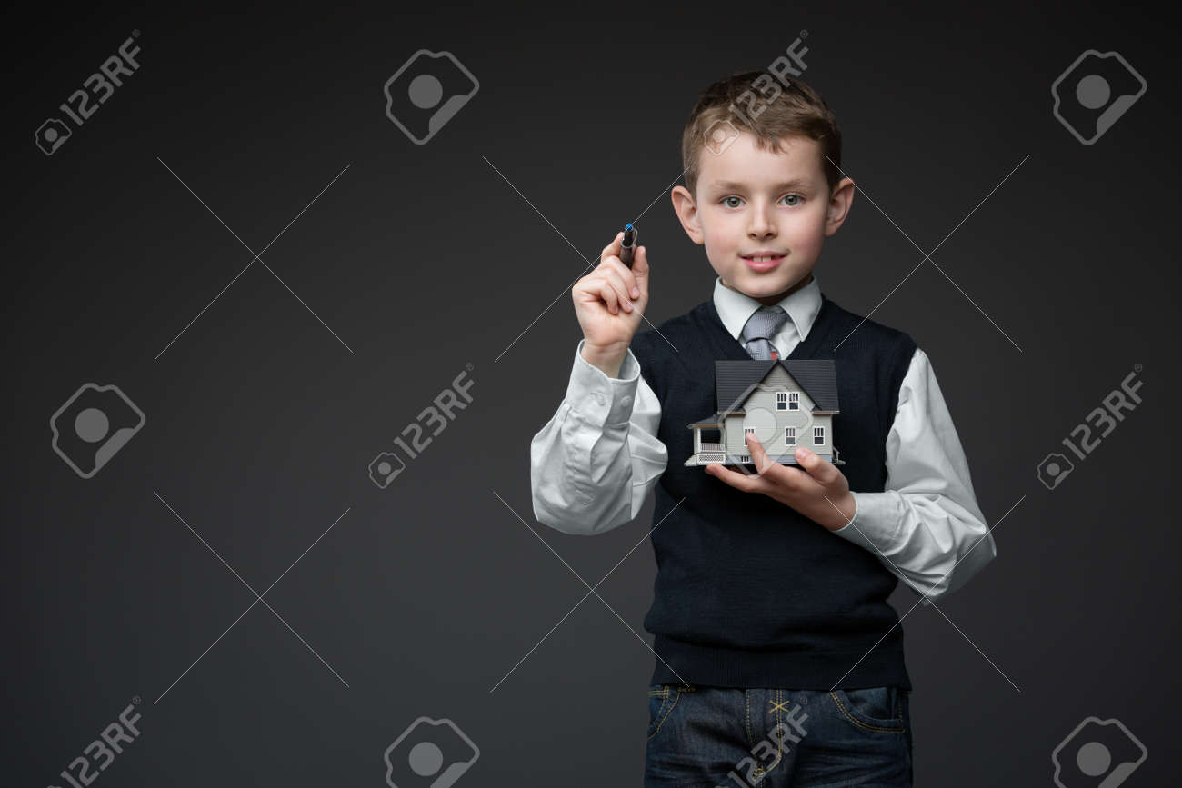 Portrait of boy writing something with chalk and keeping house model on grey background, copyspace Stock Photo - 24481324