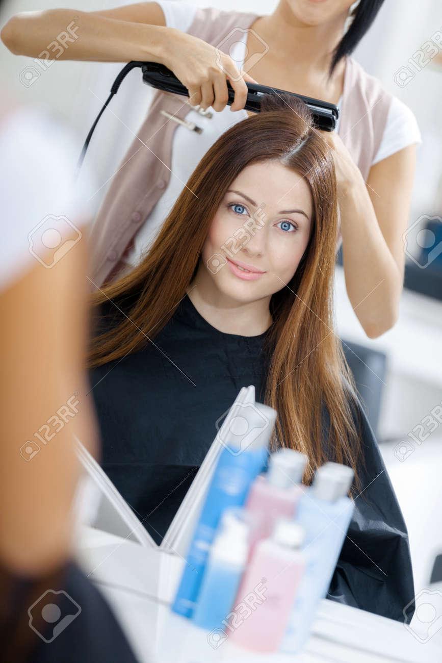 美容師の女性のための髪のスタイルをやっての反射。ファッションと美容のコンセプト
