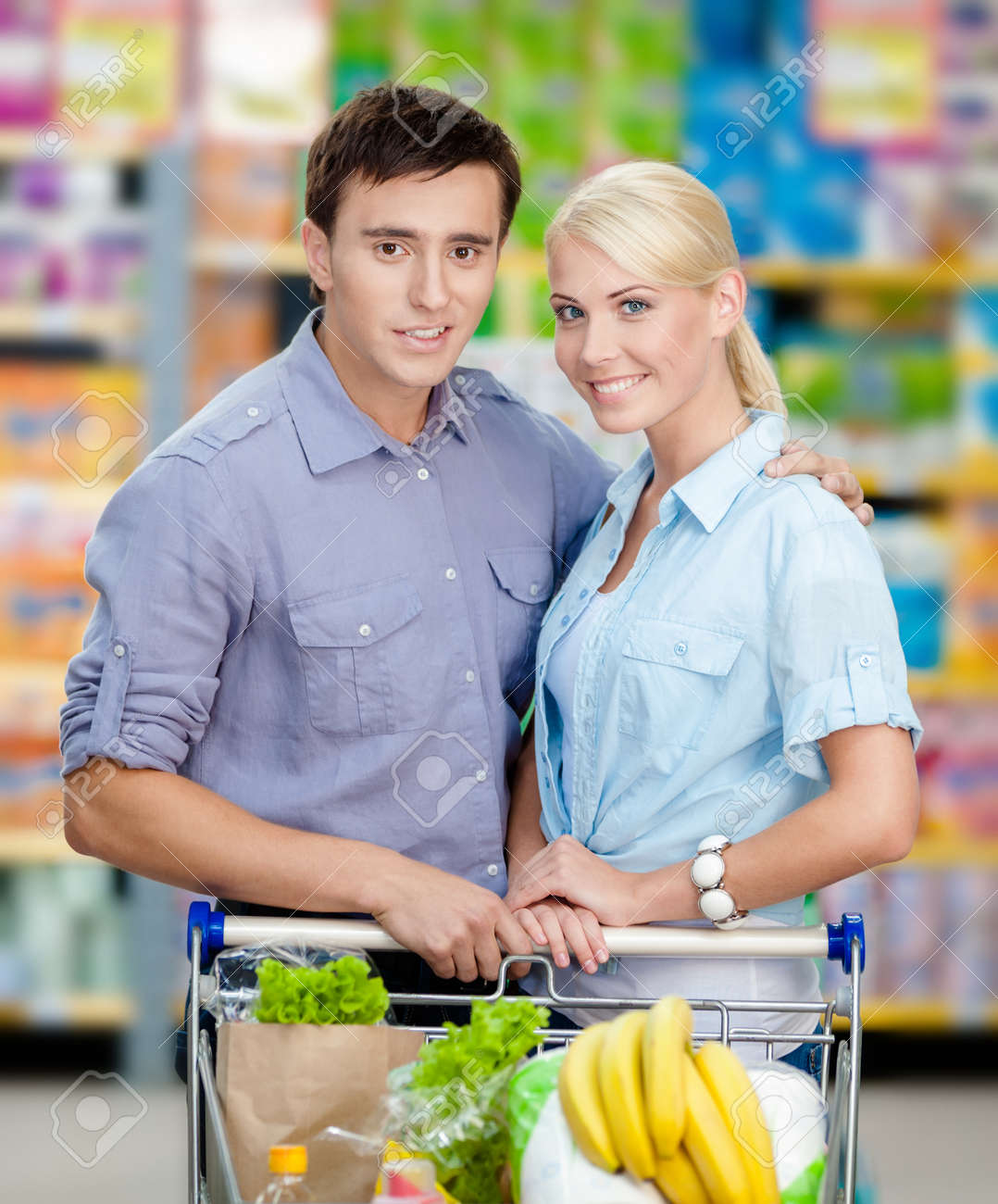 Half Length Portrait Of Couple In The Store With Cart Full Of