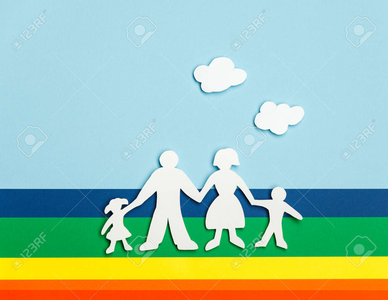 Close Up Of Happy Family Paper Dolls On Colorful Background Under Cutout Clouds Stock