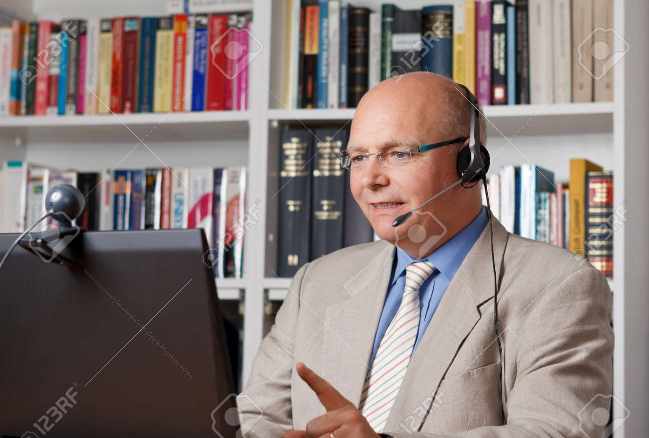 Friendly businessman with headphones in front of a computer with camera - 25745228