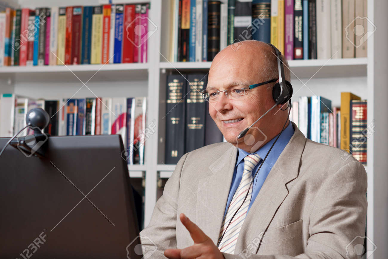 Laughing senior empoyee telephoning by means of computer, webcam und headset - 25745329
