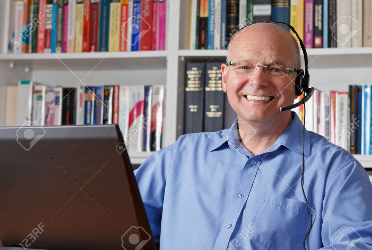 Elderly man with headphones and computer laughing happily, copyspace - 25745328
