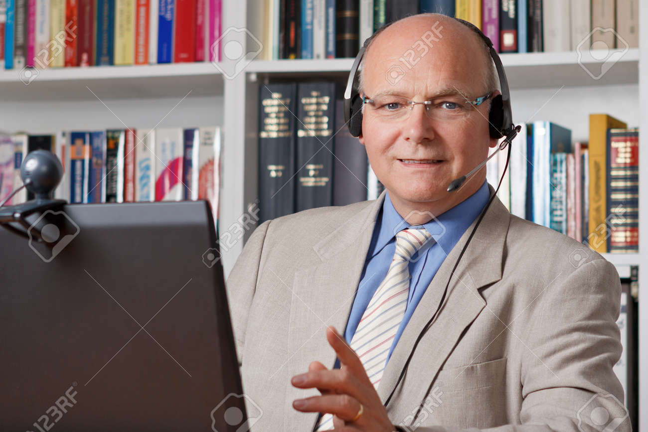 Smiling elderly businessman with computer, webcam and headset - 25746310
