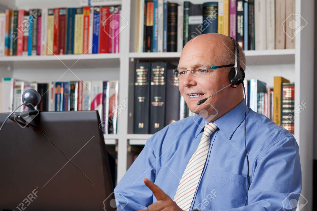 Friendly smiling man with headphones, notebook and webcam telephoning - 25746398
