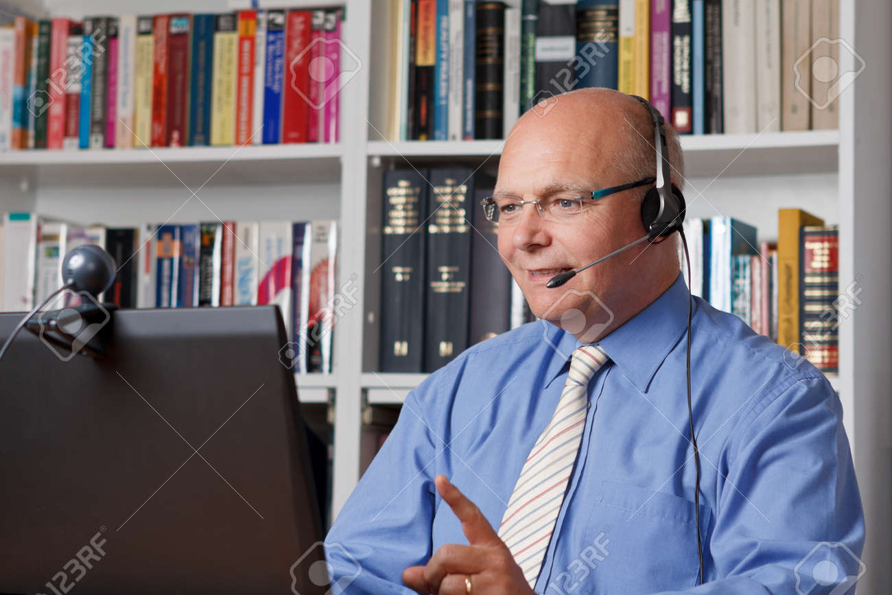 Friendly tutor talking with a student via headphones and internet - 25746502