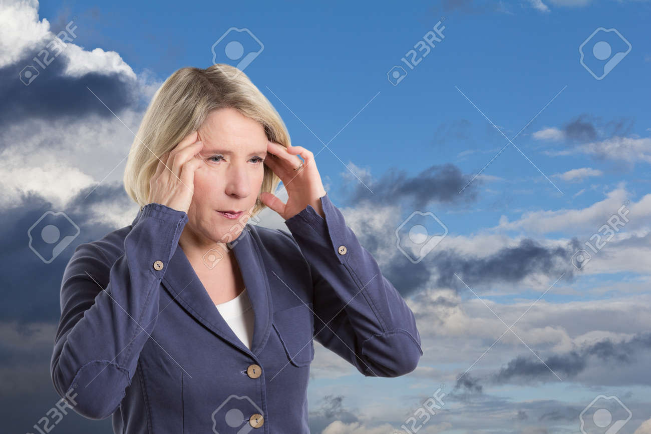 Middle aged woman being weather sensitive and suffering from a headache, copy space - 25747172