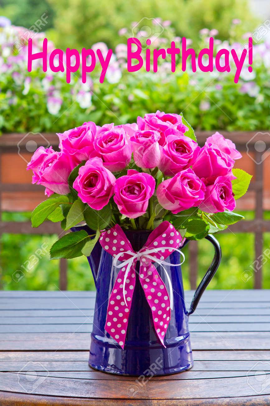 Bouquet of pink roses in a blue enamel jug with a bow of pink bouquet of pink roses in a blue enamel jug with a bow of pink ribbon outdoors izmirmasajfo