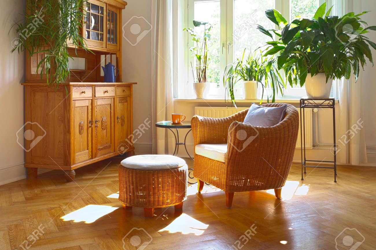 Ensoleillé salon dans des couleurs chaudes avec un fauteuil en osier et  tabouret, armoire antique et plantes