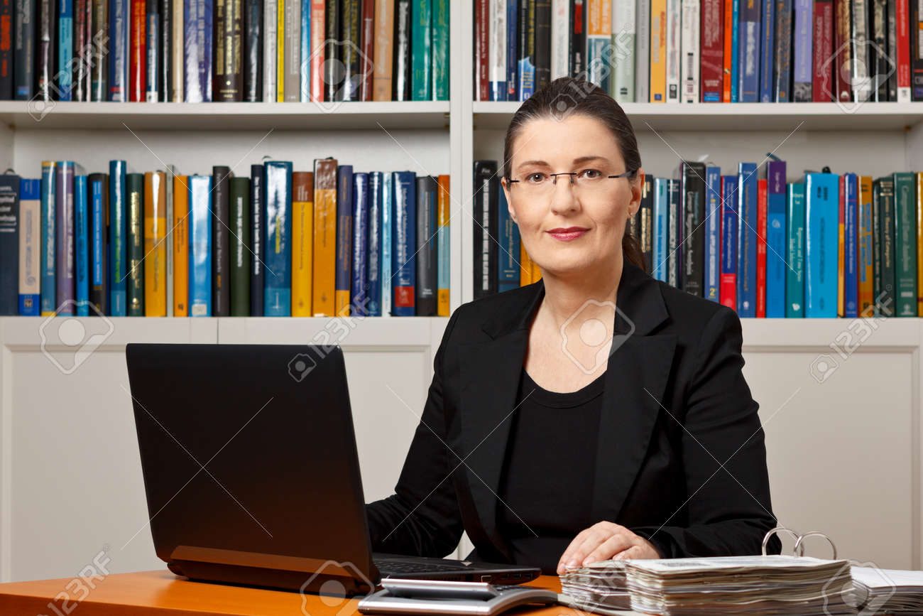 Mature woman in an office or library with laptop, calculator and files binder, tax or financial accountant, consultant, adviser or counselor - 50496510