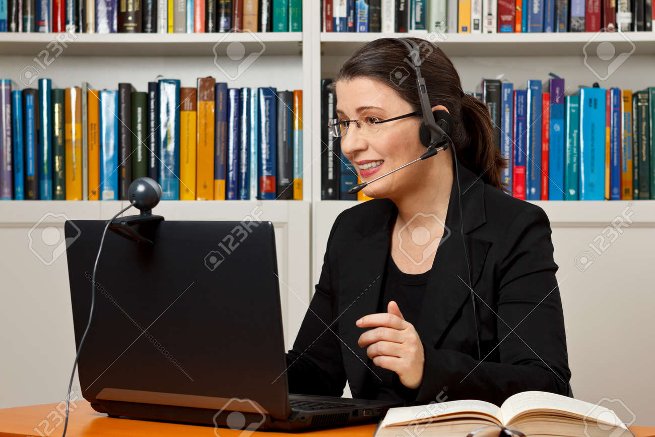 Mature woman with headset, laptop and webcam in front of a lot of books, giving online legal advice via a video call - 50496511
