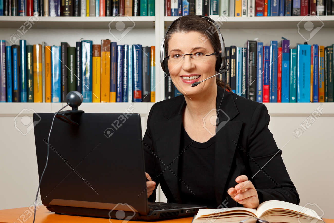 Smiling woman with headphone, computer and webcam in her office, consultant, adviser, teacher, online learning, business - 50496512