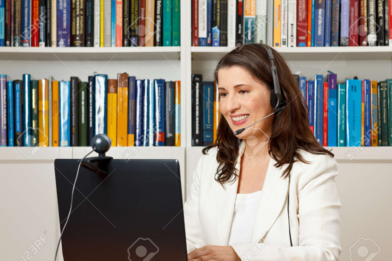 Smiling businesswoman in front of her computer in her office having a video call with her family at home, voip - 50496537