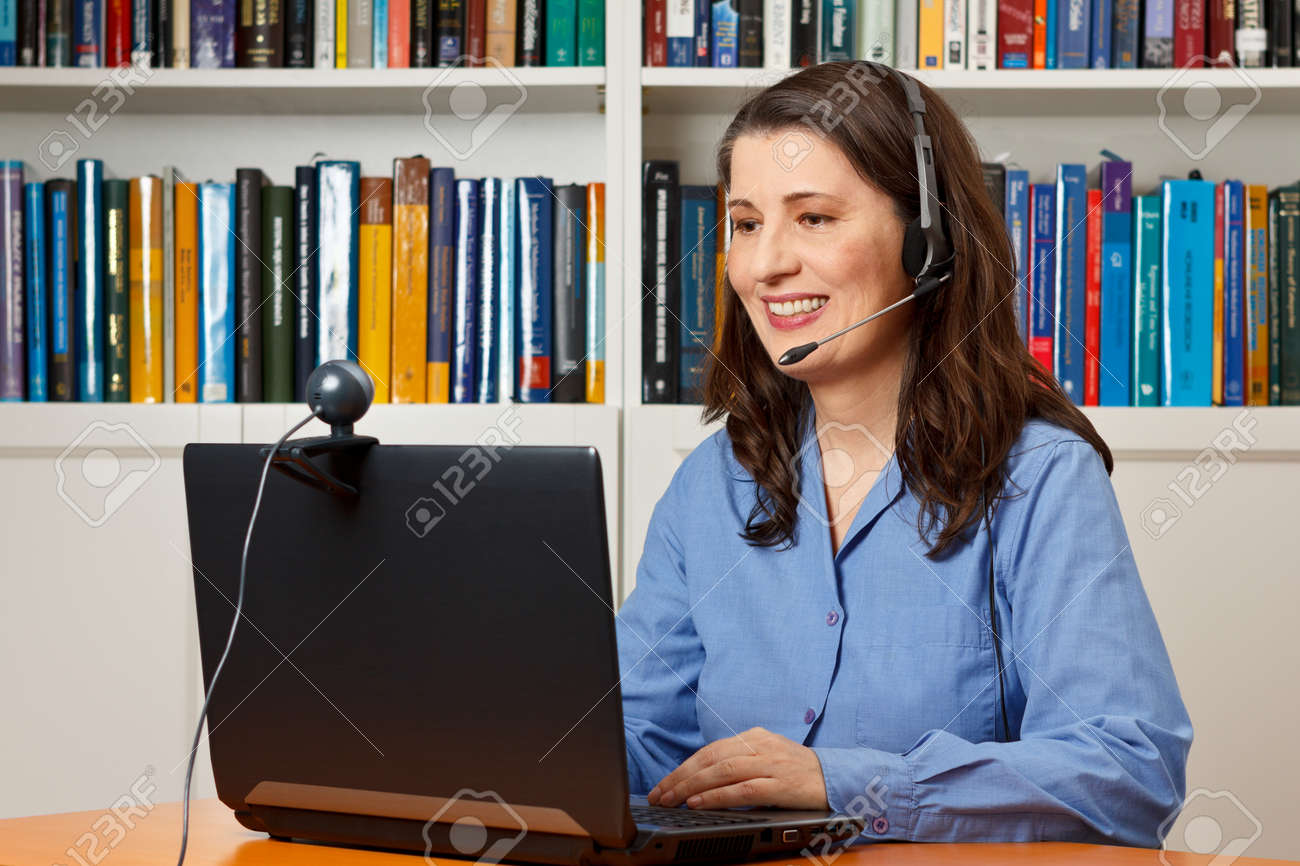 Smiling woman with laptop, camera and headset video telephoning via the internet, skype - 50497030