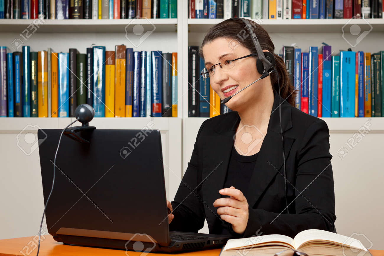 Female tutor or teacher with headset, computer and camera in her office talking with a student via video telephony, skype - 50497032