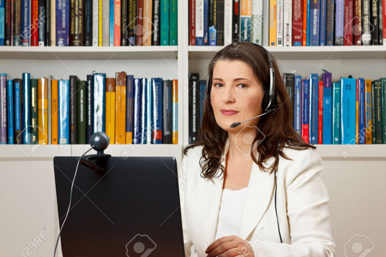 Middle aged woman with headset in front of her computer with webcam in a library, consultant, teacher, tutor, online course - 50497035