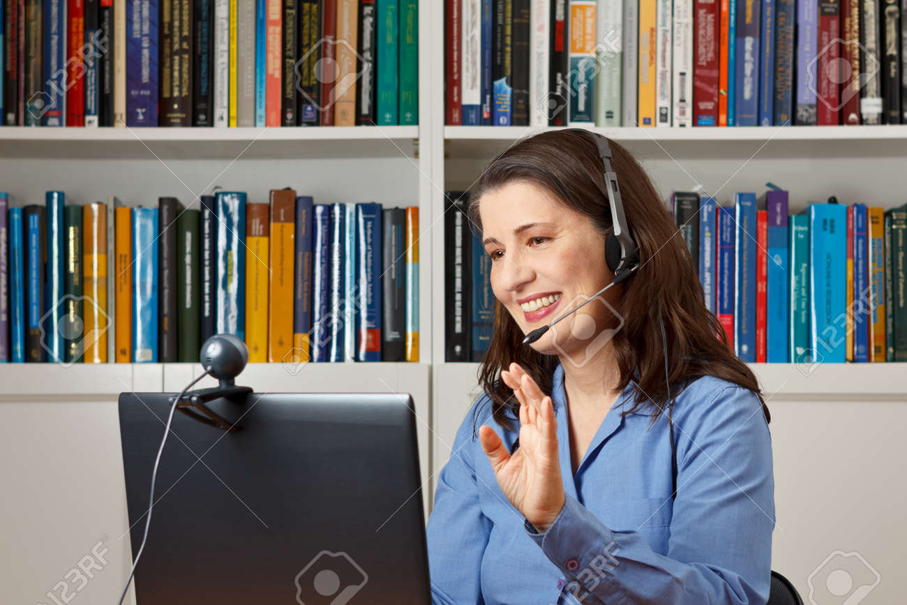 Smiling woman in her office with laptop, camera and headset telephoning with her children via the internet - 50497036