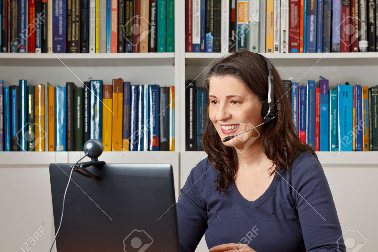 Middle aged woman with computer, headset and webcam talking with friends via viewphone - 50497040