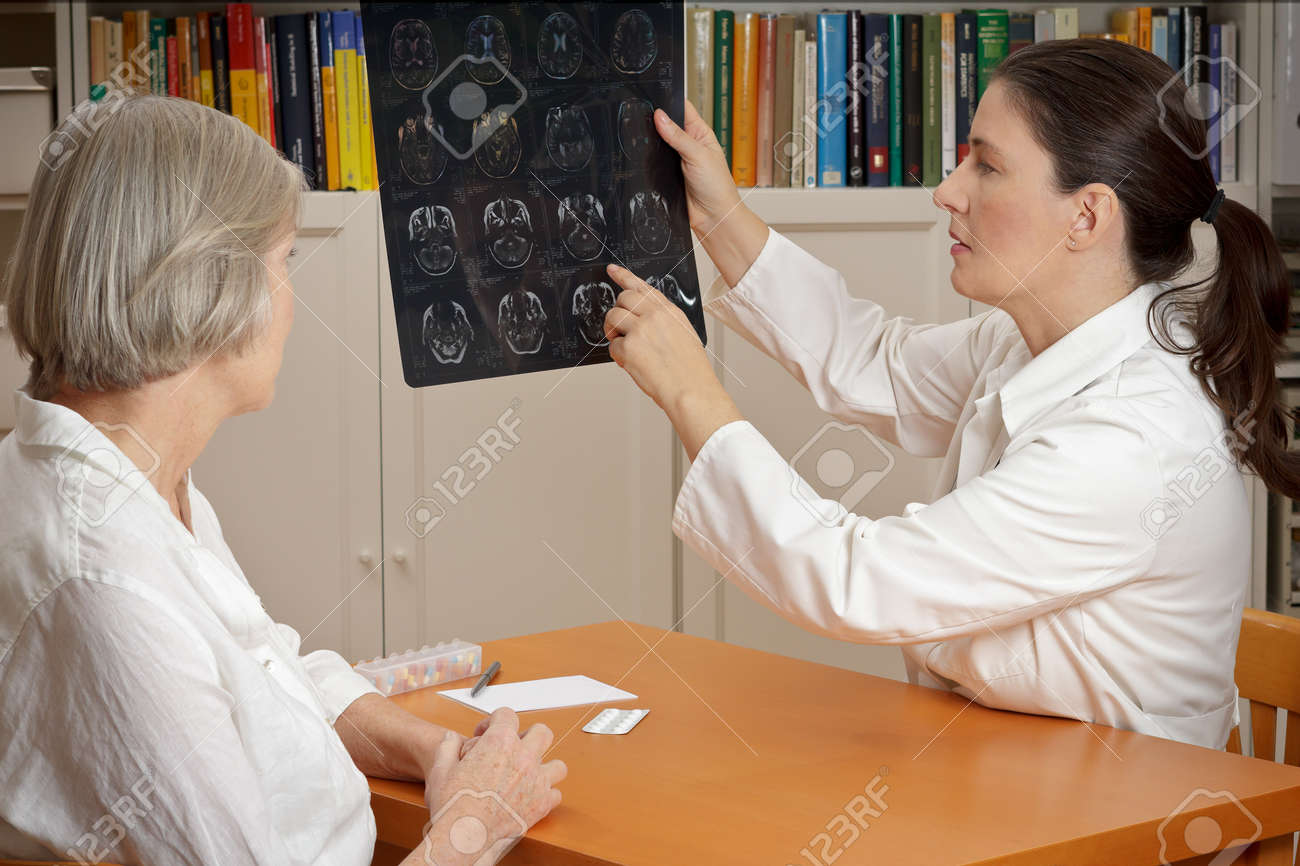 2 women in a surgery: middle aged doctor in lab coat showing her senior patient magnetic resonance images of her head - 65805360