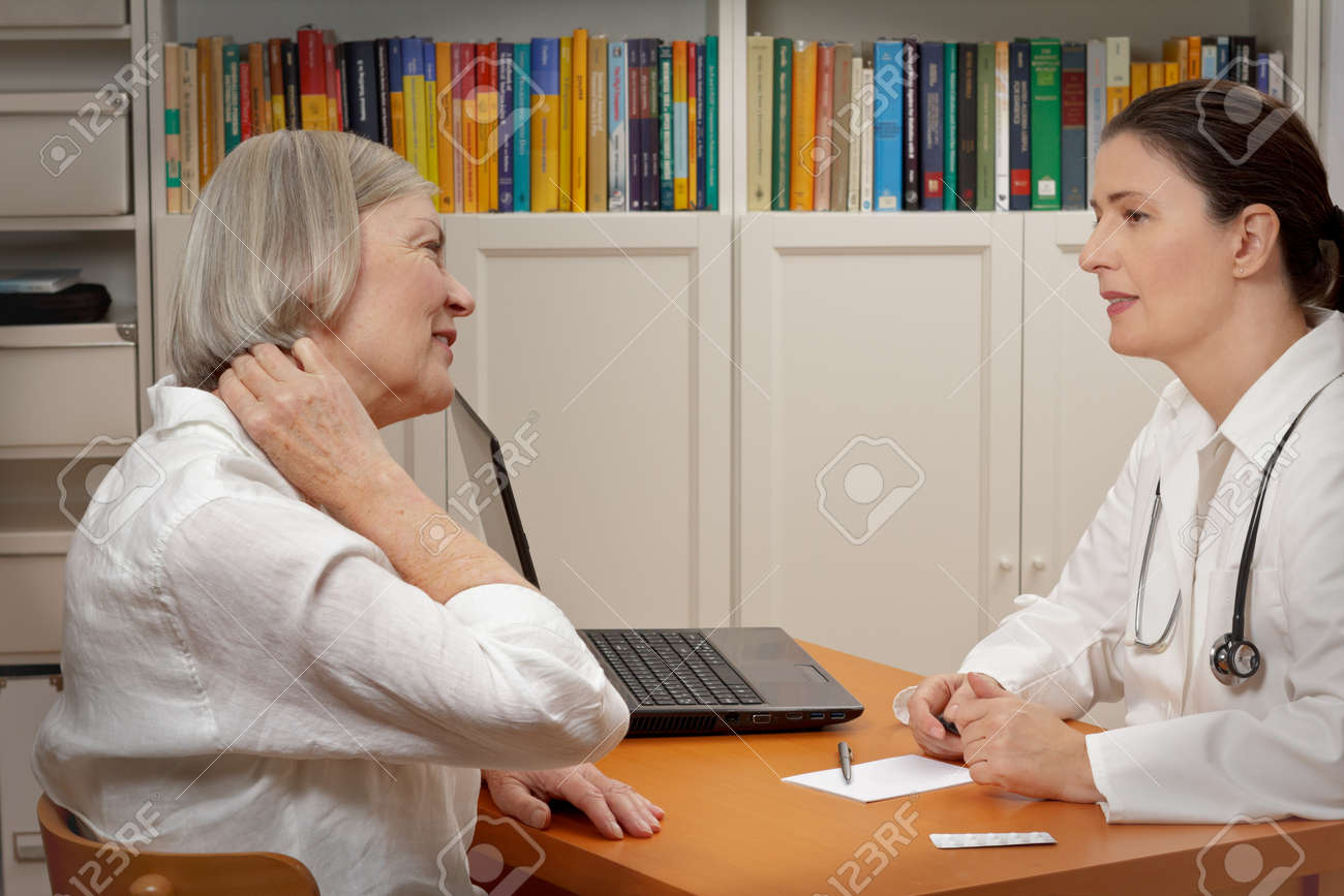 Senior female patient consulting middle aged doctor because of strong neck pain caused by muscular tension - 65805385