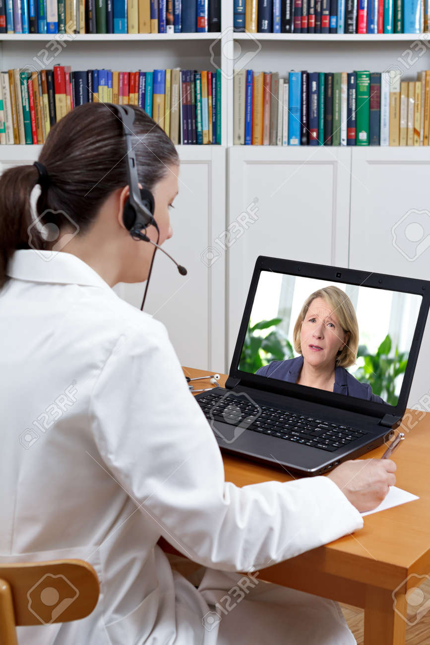 Doctor at a pain management center in her office with headset and laptop, listening to patient in agony with strong backache, telemedicine concept - 72652959