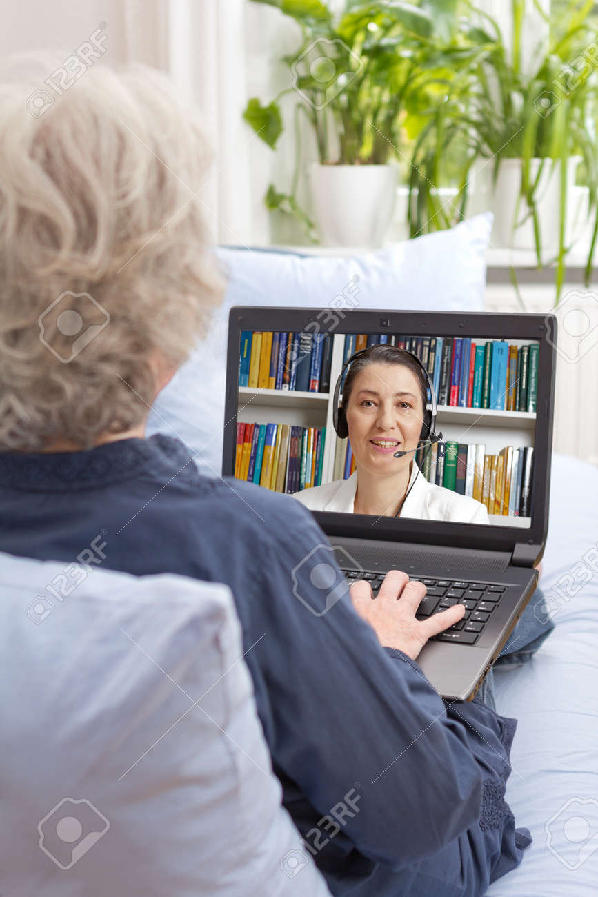 Rear view of a senior woman sitting with laptop on the sofa of her living room, having an online therapy session via the internet, psychological helpline - 71369220