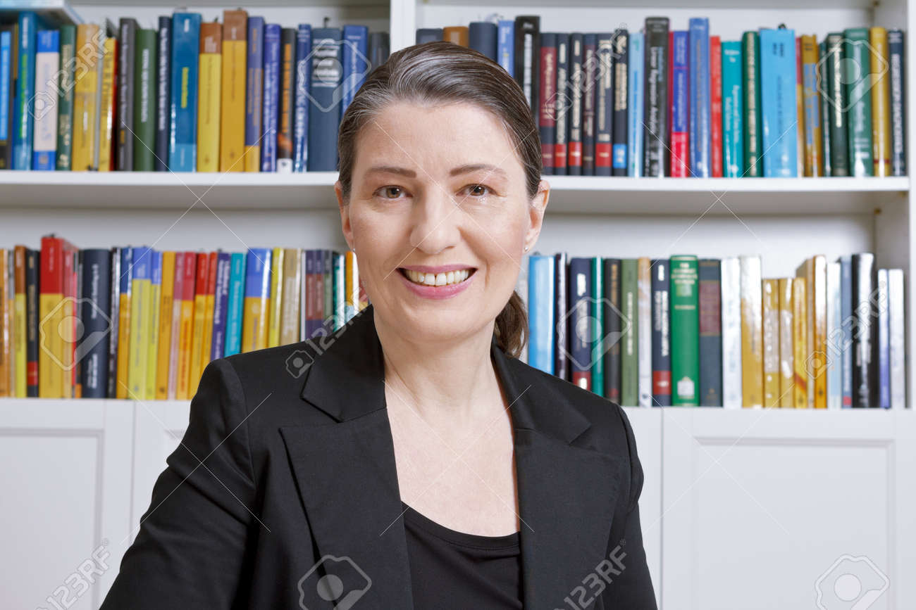 Friendly smiling mature woman with black blazer in an office with lots of books, professor, teacher, translator, lawyer, accountant or businesswoman - 73904550