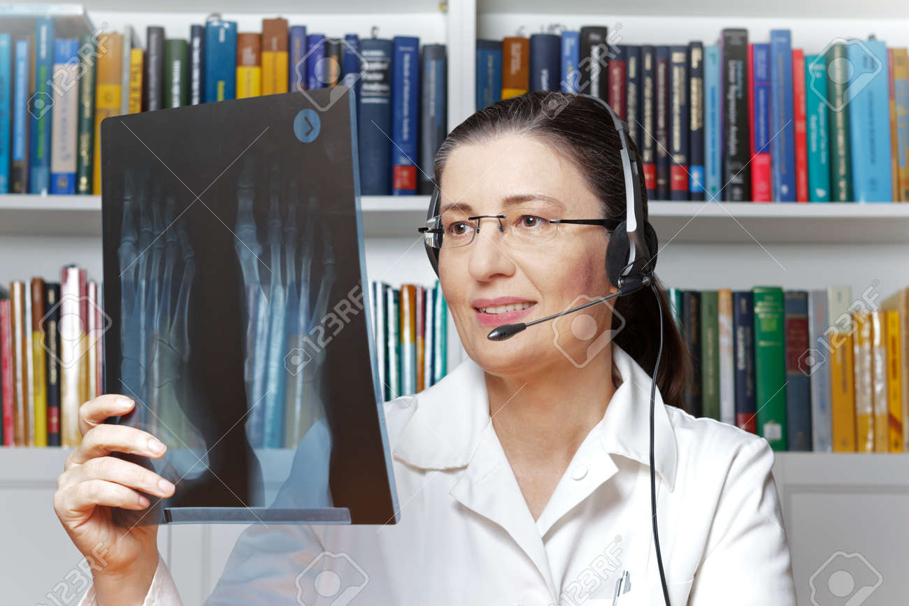 Female doctor or radiologist with headset and an x-ray of a foot in hand as seen through a webcam, telehealth concept - 73904554