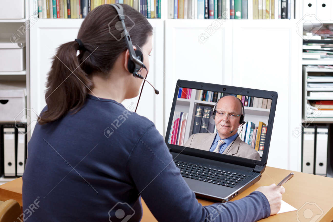 Woman with pen and paper and a headset in front of her laptop making a video call with her friendly professor, text space - 79662354