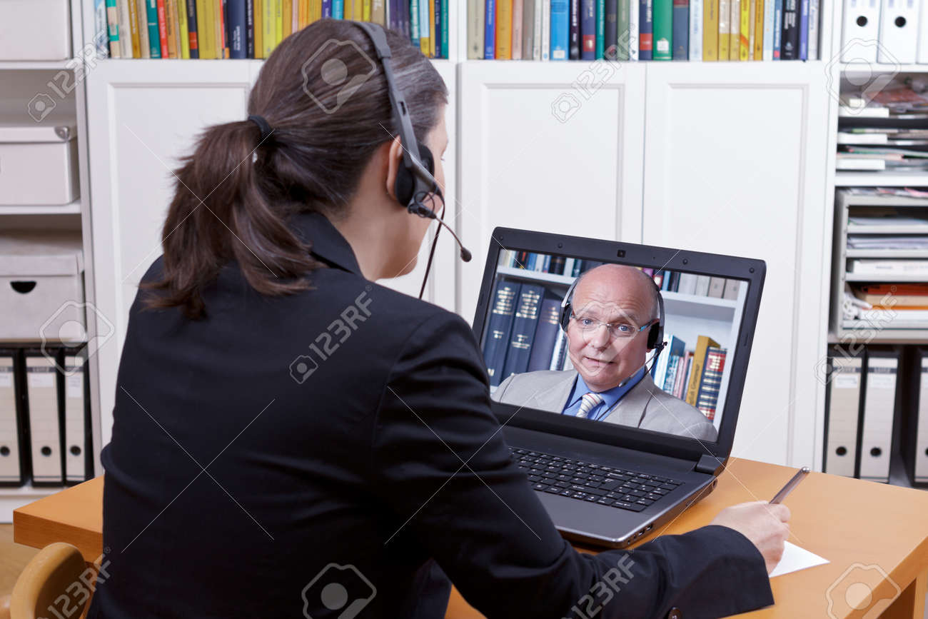 Woman with headset in front of her laptop writing something on a paper while making a live video call with a client or colleague, copy space - 79661182