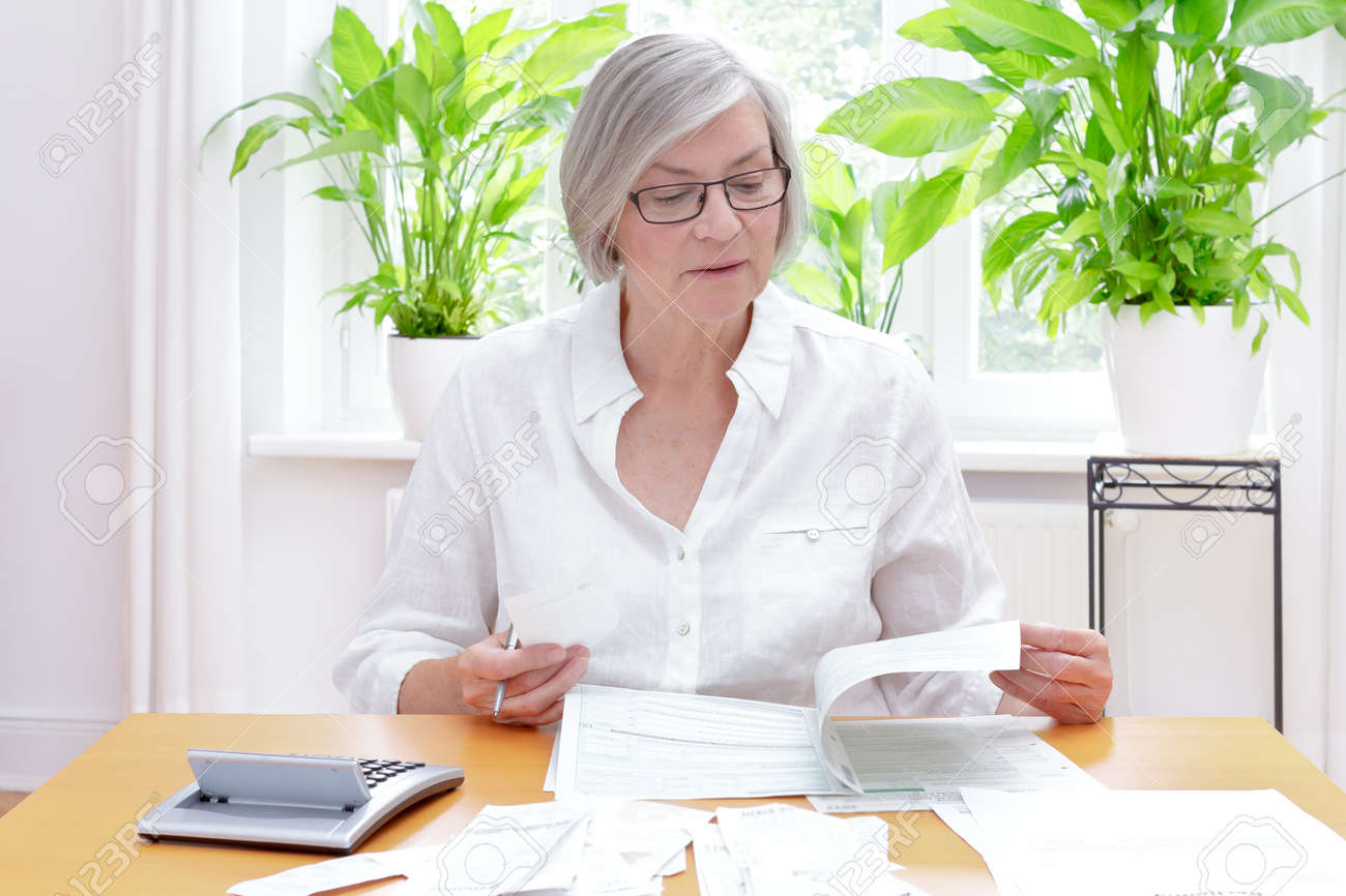 Senior german woman at home with a calculator and lots of bills and receipts, filling out the printed forms of the annual tax declaration - 81728544