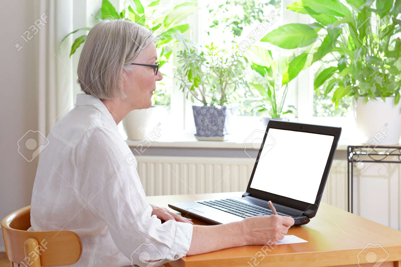 Senior woman at home in front of her laptop taking notes, online advice or e-learning concept template, white screen, copy space - 81728545