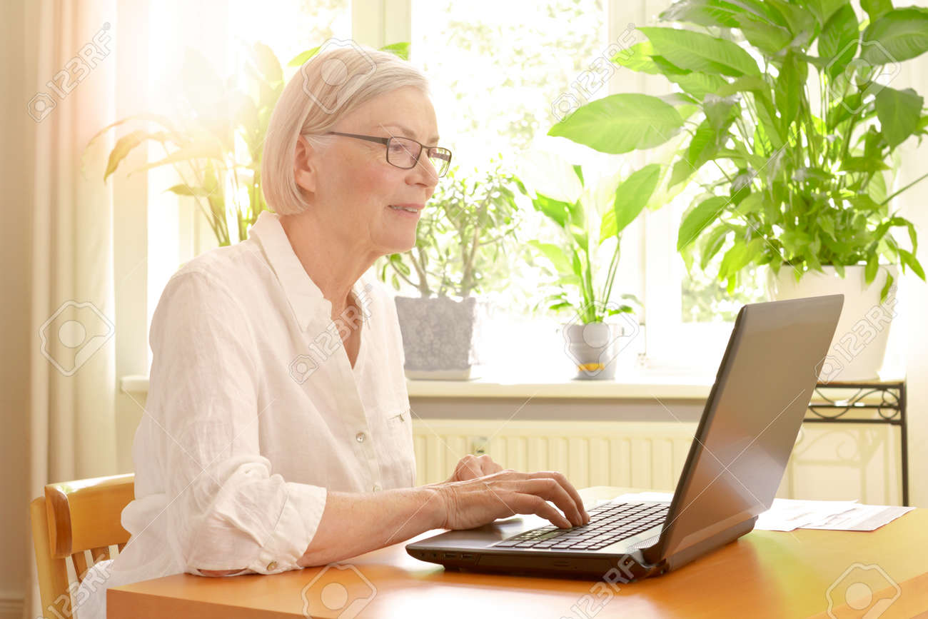 Happy senior woman in her sunny living room in front of her laptop enjoying the benefits of good financial planning for a carefree retirement - 81728554