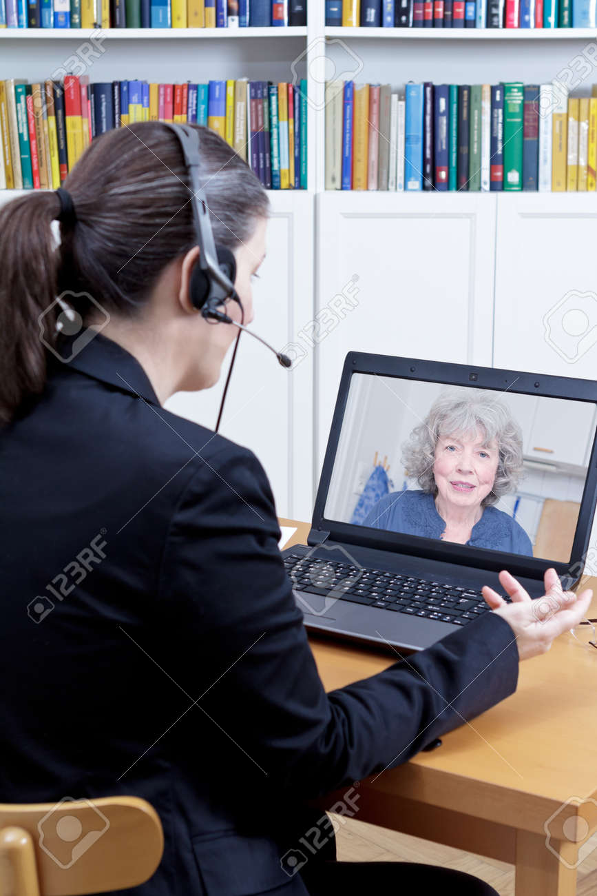 Female psychologist with headset in her office in front of her computer, talking to a senior woman during a live video call or chat, online counseling session template - 83563467