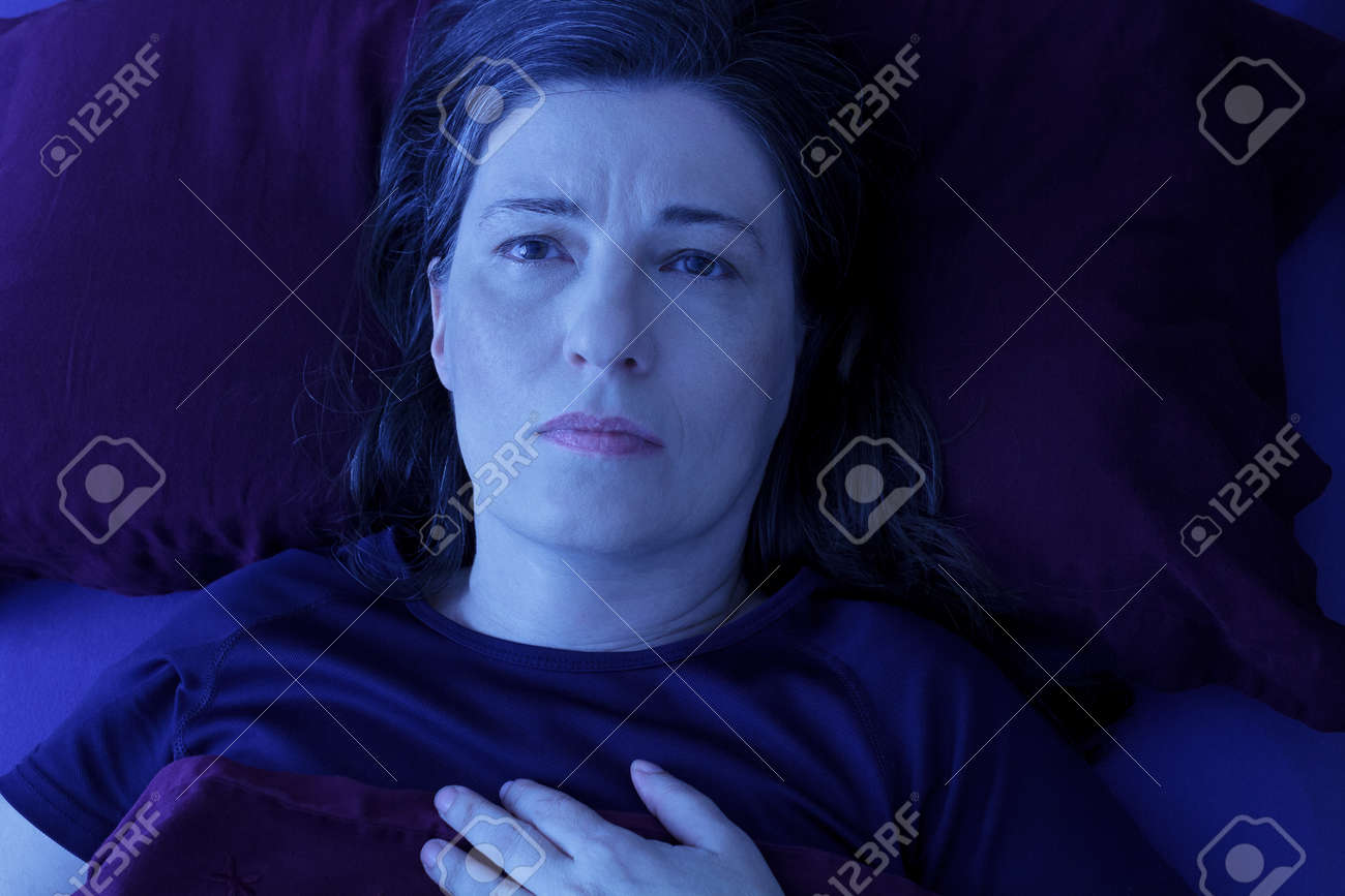 Middle aged woman lying awake in her bed at night because of insomnia, stress, fears, nightmares or restless leg syndrome - 92140006