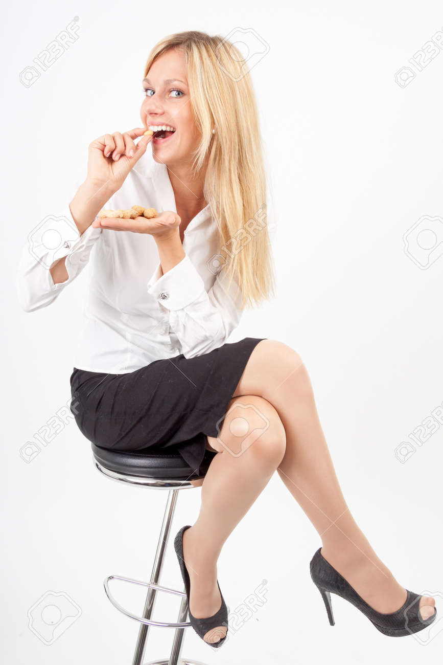 Young woman eating peanuts out of her hand