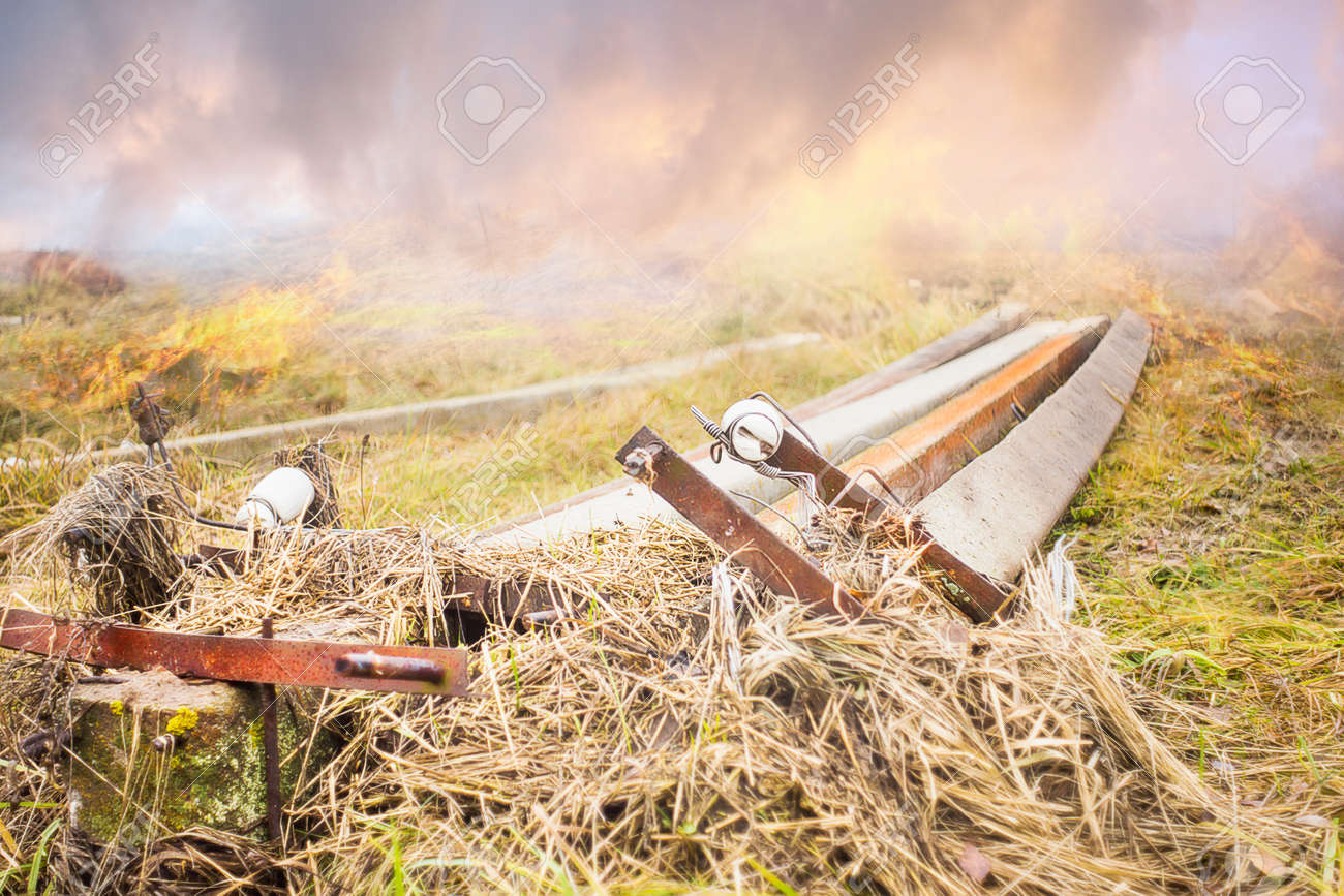 Old Electric Poles And A Fire In The Dry Autumn Grass Smoke Stock