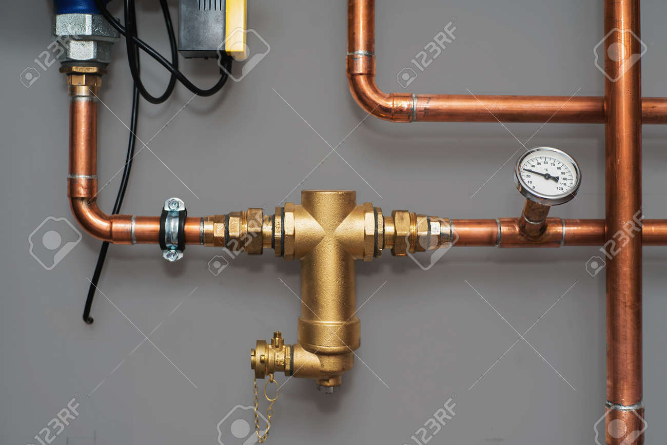 Thermometer and water filter for central heating system on a grey wall in a boiler room. Close up. - 93295413
