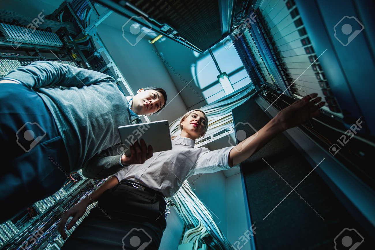 Young engineers businessmen in network server room - 51169208