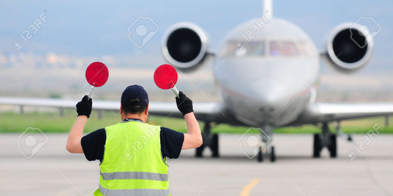 Air traffic controller holding signs at the airport - 52463347