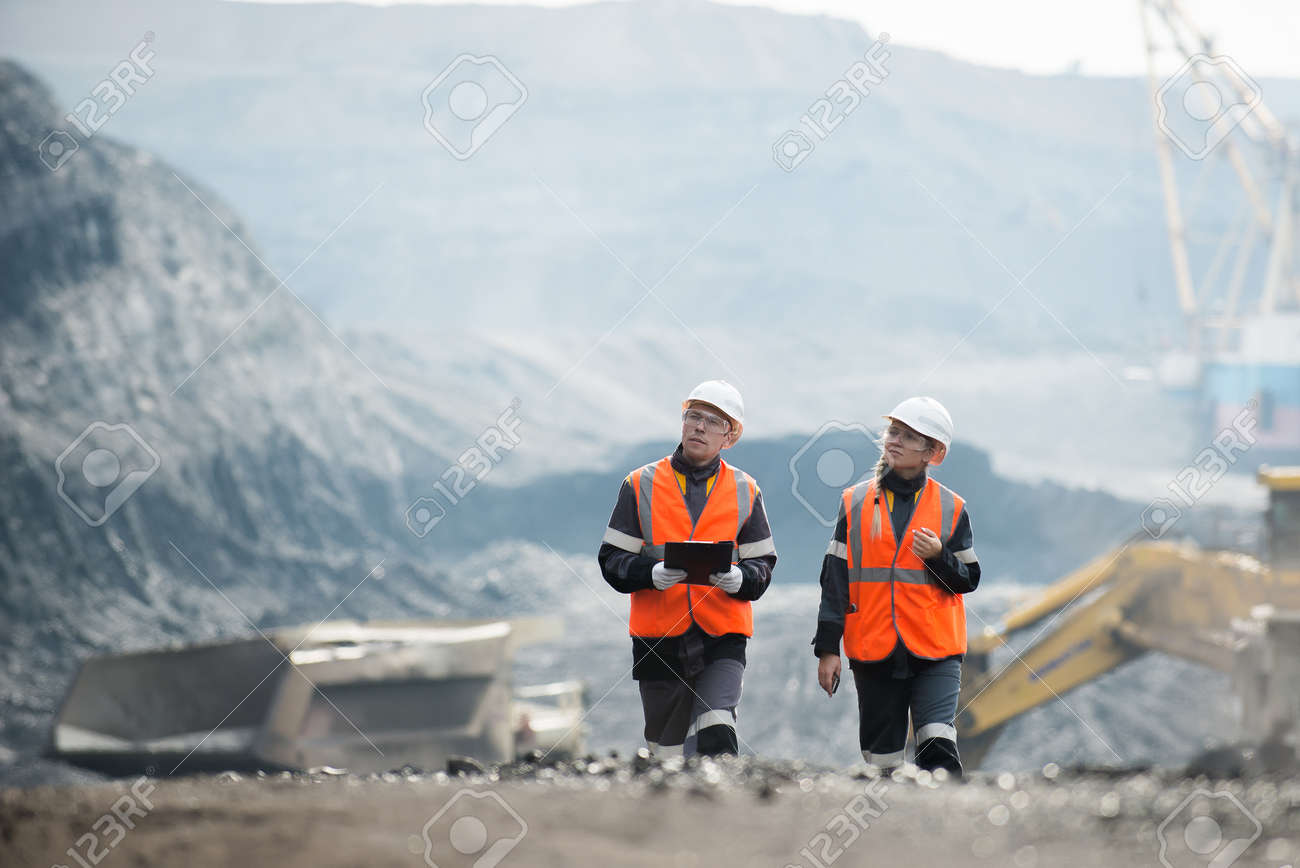Two speacialists examining coal at an open pit - 61160446