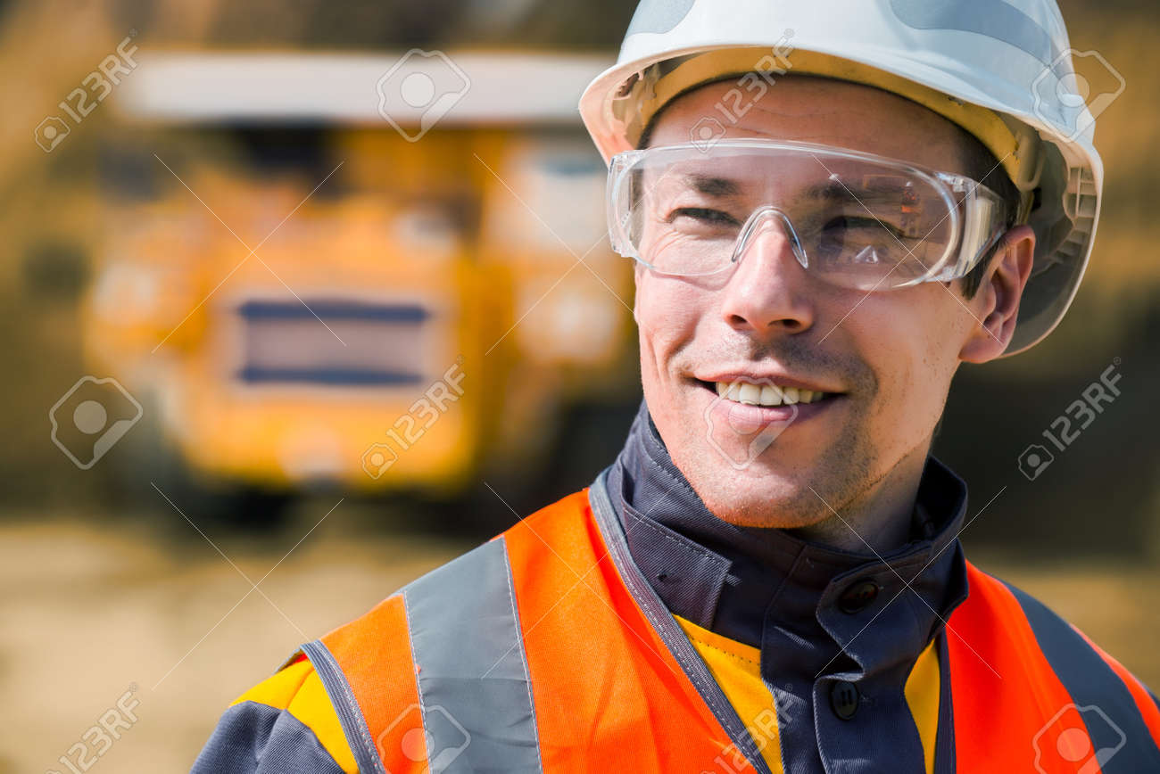 Mine worker with huge truck on the background in open pit - 63850917