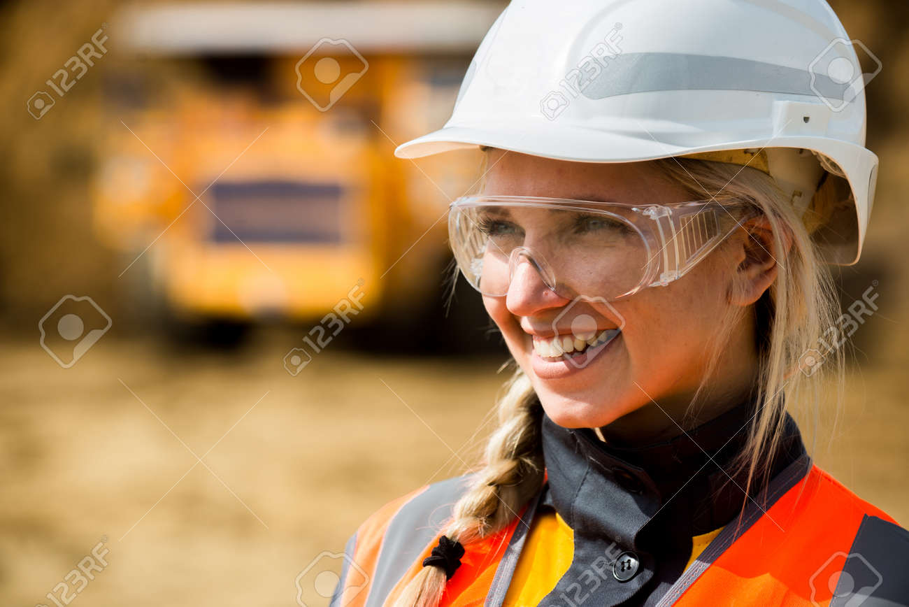 Mine worker with huge truck on the background in open pit - 63876504