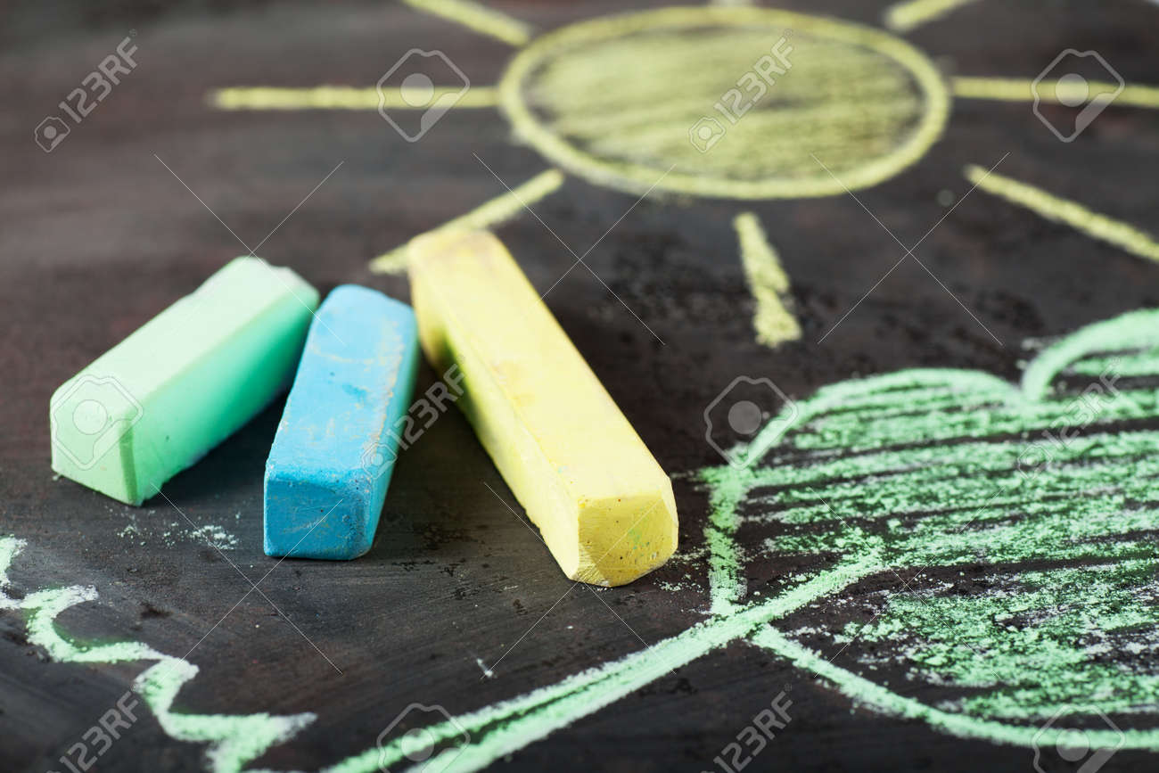 Sun and tree drawing and chalks on a blackboard Stock Photo - 12977801