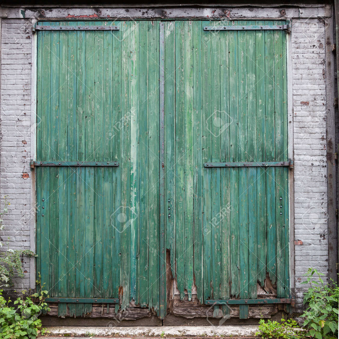 Large Old Barn Doors With Peeling Green Paint In White Brick Stock